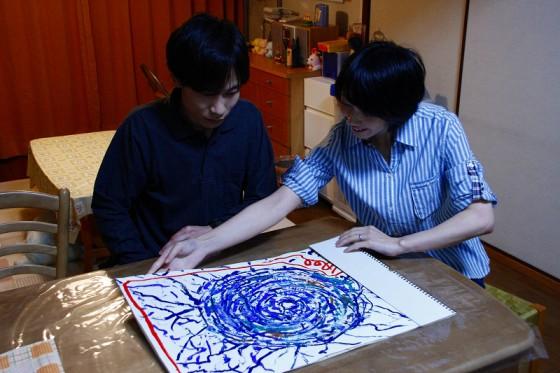 自閉症の長男が描いた「蜘蛛の巣」を見る夫婦。 この絵は映画のテーマの一つにもなっている。